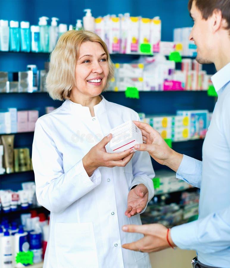 Pharmacien féminin conseillant le client au sujet de l'utilisation de drogues photo libre de droits