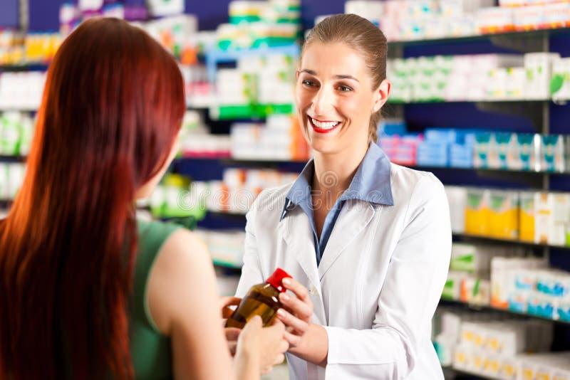 Pharmacien féminin dans sa pharmacie avec un client image libre de droits
