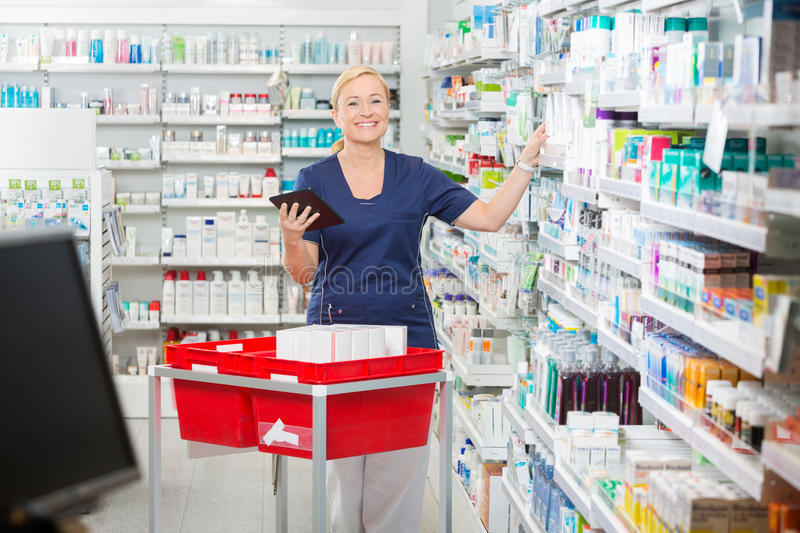 Pharmacien féminin heureux Updating Stock In Digital photographie stock libre de droits