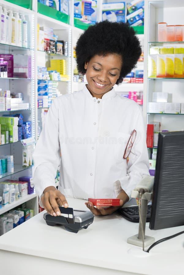 Pharmacien féminin Swiping Credit Card tout en tenant le produit images libres de droits