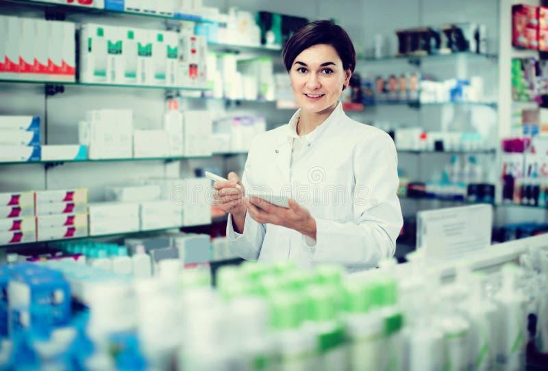 Pharmacien féminin vérifiant l'assortiment des drogues dans la pharmacie photo stock
