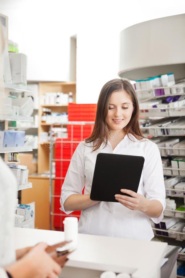 Pharmacien Helping Customer avec la Tablette de Digital photo stock