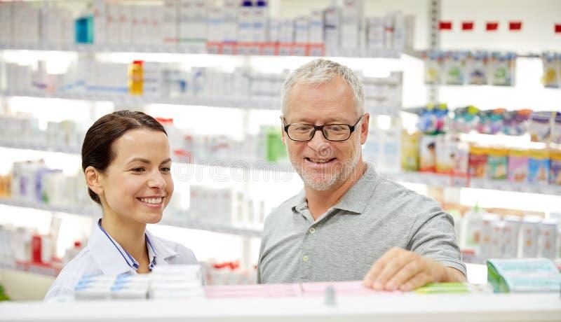 Pharmacien heureux parlant à l'homme supérieur à la pharmacie images stock