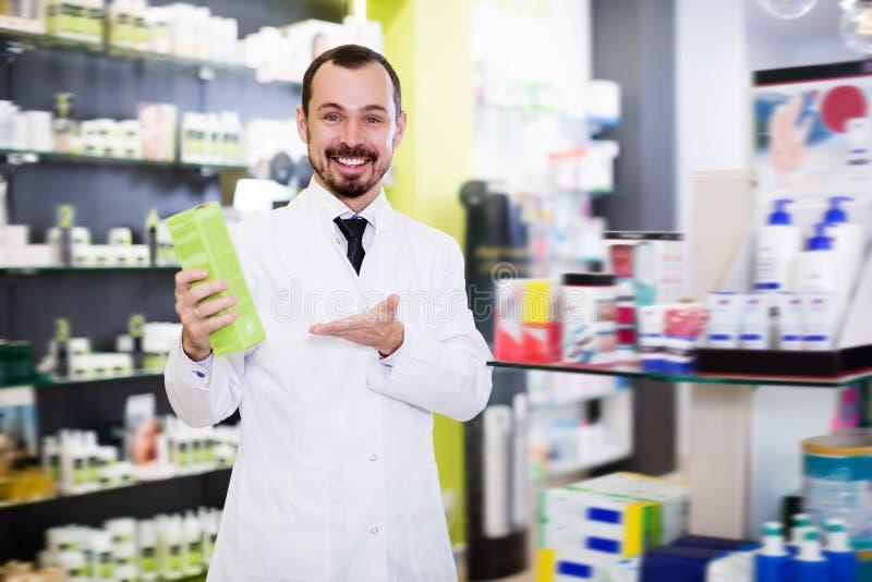 Pharmacien heureux proposant la drogue utile photos stock