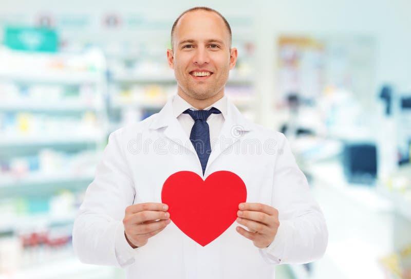 Pharmacien masculin avec le coeur à la pharmacie photographie stock libre de droits