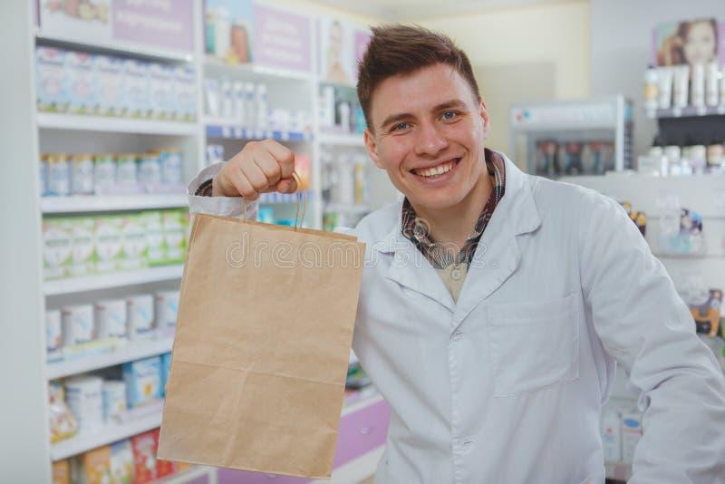 Pharmacien masculin beau travaillant à sa pharmacie photo stock