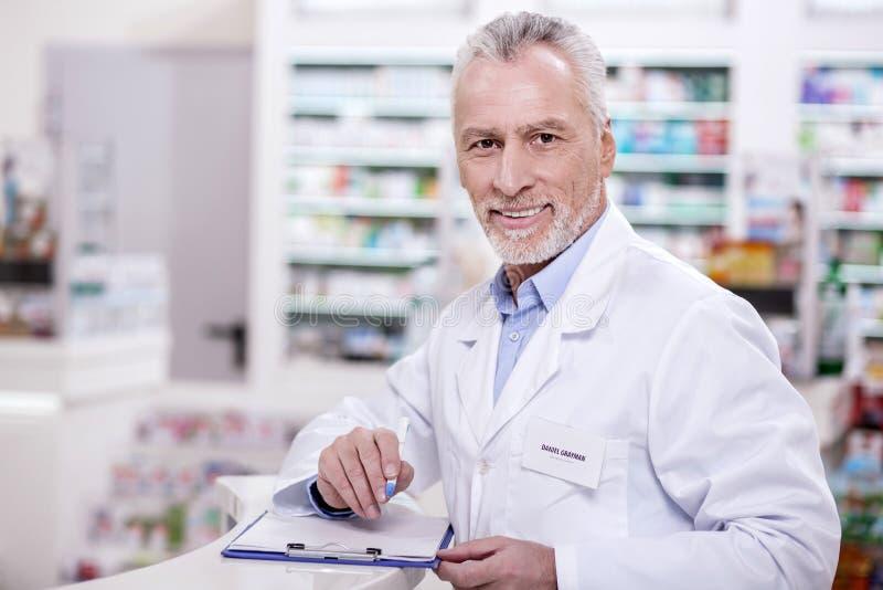 Pharmacien masculin optimiste remplissant vers le haut de la documentation image libre de droits