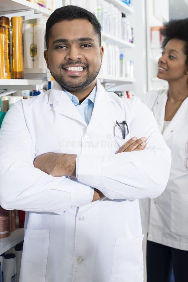 Pharmacien masculin sûr With Arms Crossed dans la pharmacie images libres de droits