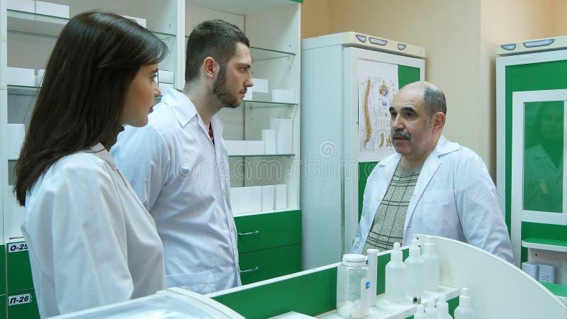 Pharmacien masculin supérieur aidant ses jeunes collègues à la pharmacie photo stock