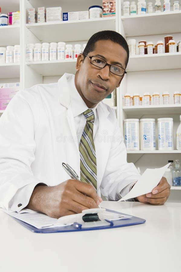 Pharmacien masculin travaillant dans la pharmacie images libres de droits