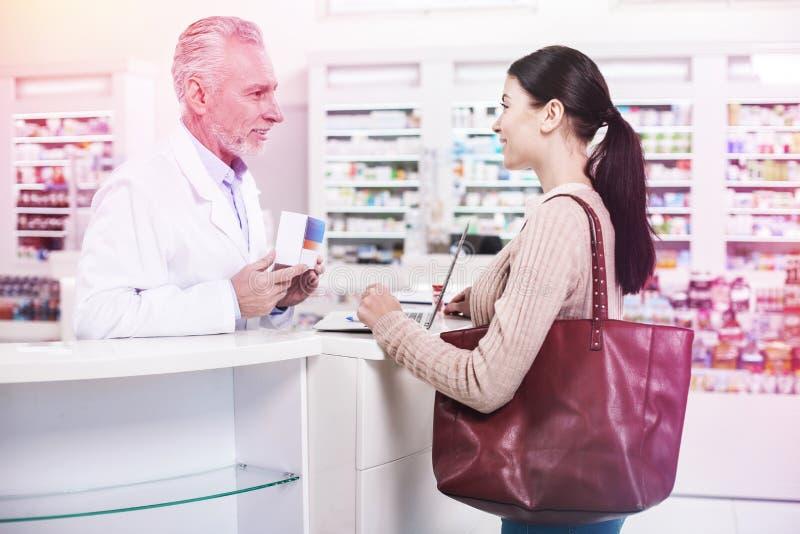 Pharmacien montrant la boîte de médecine à un client images stock