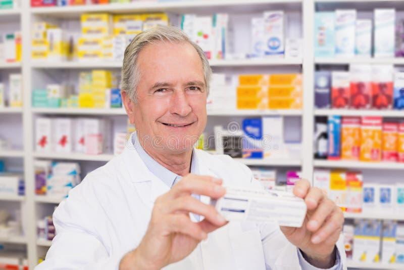 Pharmacien montrant la boîte de médecine photo stock