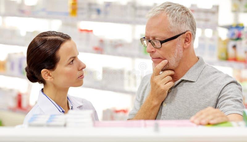 Pharmacien montrant la drogue à l'homme supérieur à la pharmacie photographie stock libre de droits