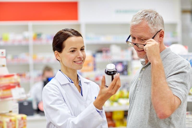 Pharmacien montrant la drogue à l'homme supérieur à la pharmacie photo libre de droits