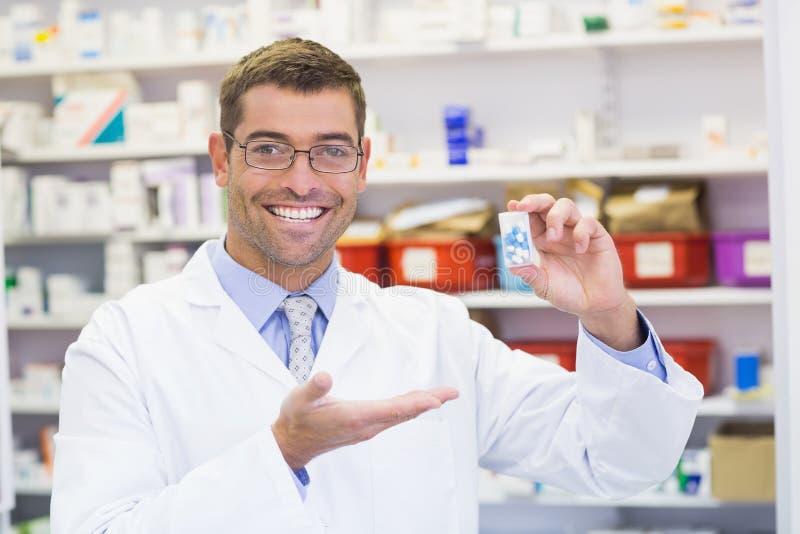 Pharmacien montrant le pot de médecine images libres de droits