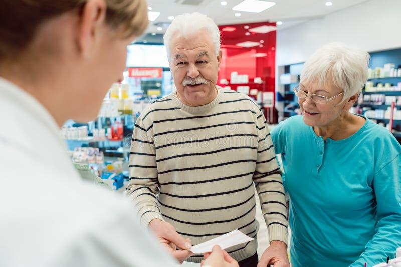 Pharmacien obtenant le glissement de prescription des couples supérieurs images stock