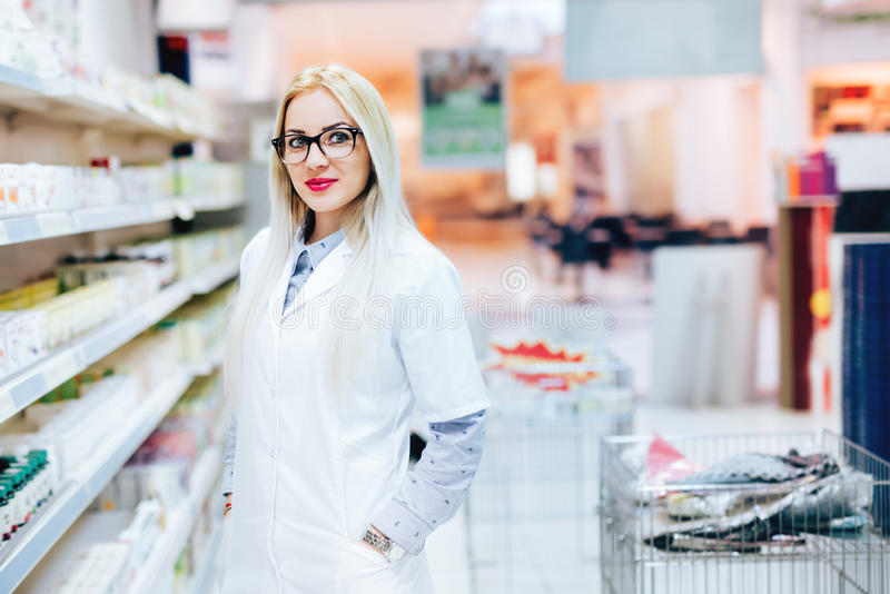 Pharmacien professionnel se tenant dans la pharmacie et le sourire de pharmacie Détails d'industrie pharmaceutique images stock