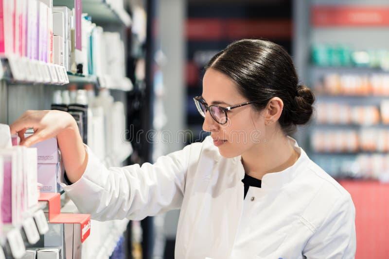 Pharmacien se tenant devant de divers produits pensant pour le meilleur choix photos stock