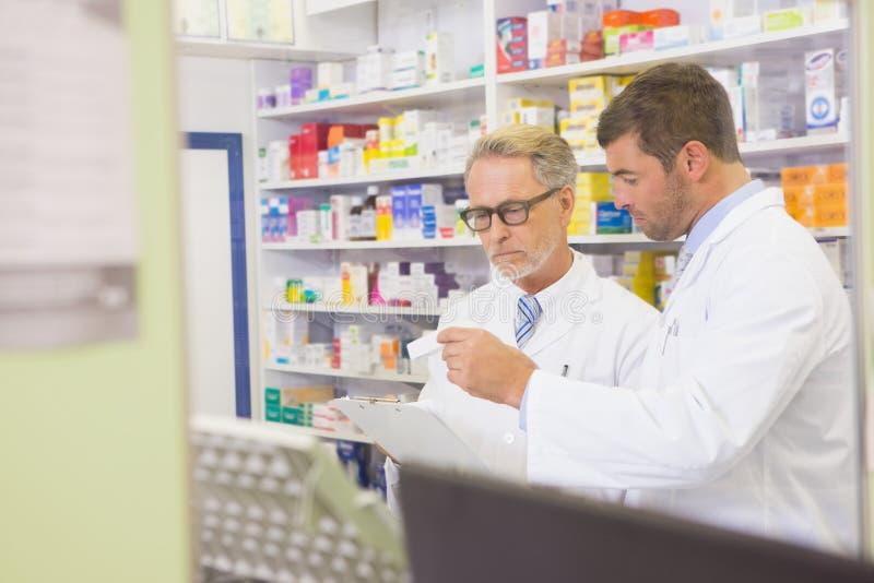 Pharmacien supérieur lisant une prescription sur le presse-papiers images stock