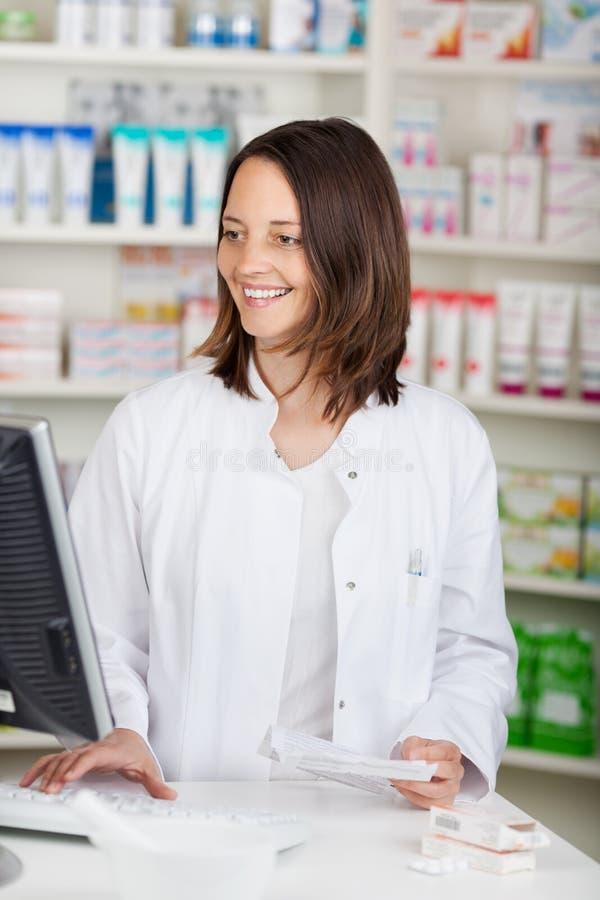 Pharmacien Using Computer While tenant le papier de prescription au De photos stock