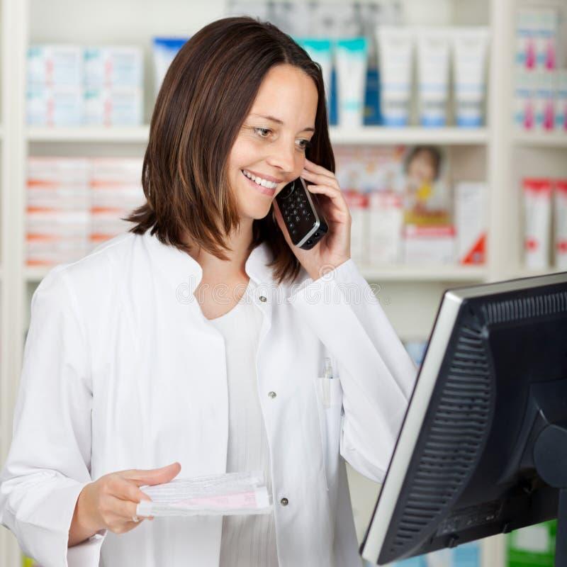 Pharmacien Using Cordless Phone tout en regardant l'ordinateur photo libre de droits
