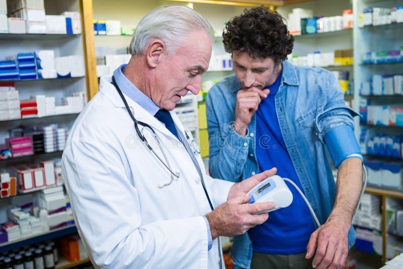 Pharmacien vérifiant la tension artérielle du client photographie stock libre de droits
