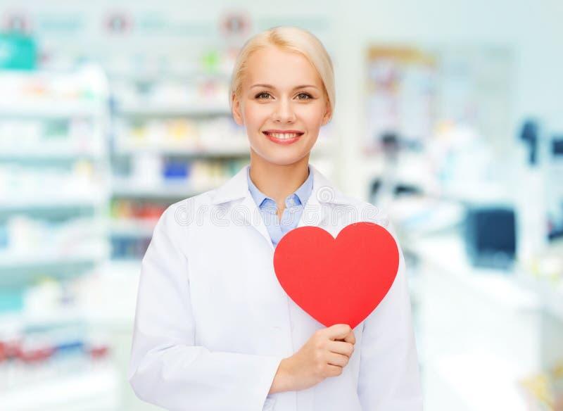 Pharmacienne de femme avec le coeur à la pharmacie images stock