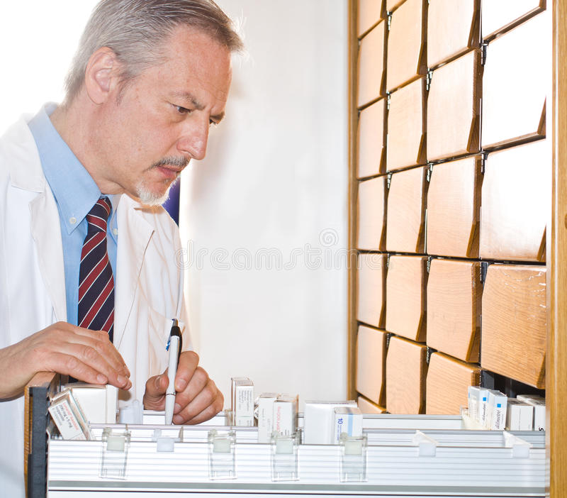 Pharmacist. Portrait of an handsome senior pharmacist searching a medicine stock photography