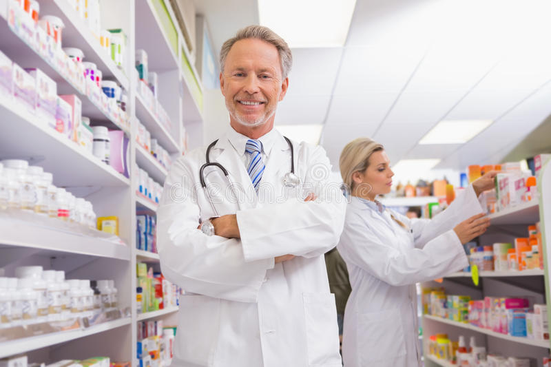 Pharmacist With Arms Crossed And Trainee Behind Stock Image - Image ...