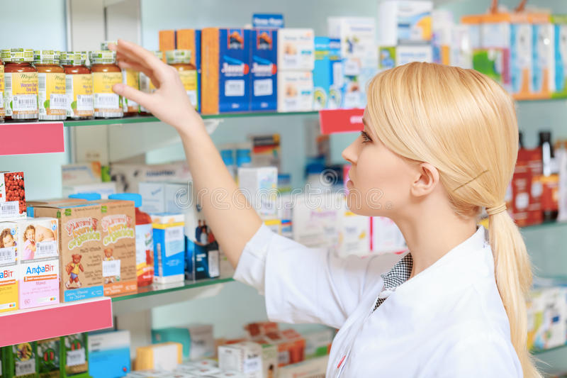 Pharmacist arranging medicines on the shelves. Searching for a right medicine. Portrait of beautiful blonde female pharmacist reading a label of the medicines in royalty free stock images