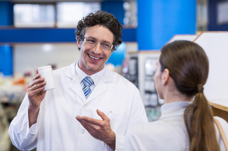 Pharmacist assisting the bottle of drug to customer. In pharmacy royalty free stock photos