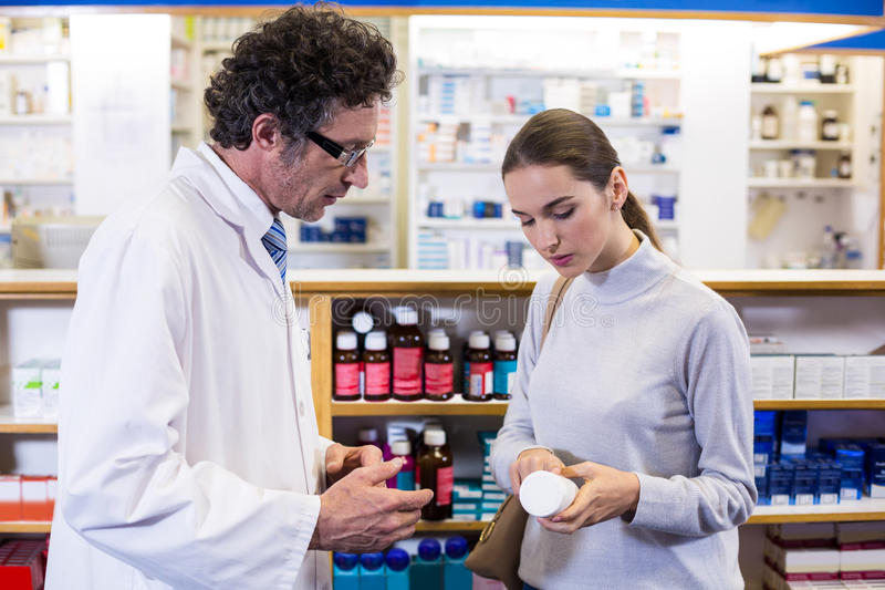 Pharmacist assisting the bottle of drug to customer. In pharmacy royalty free stock images