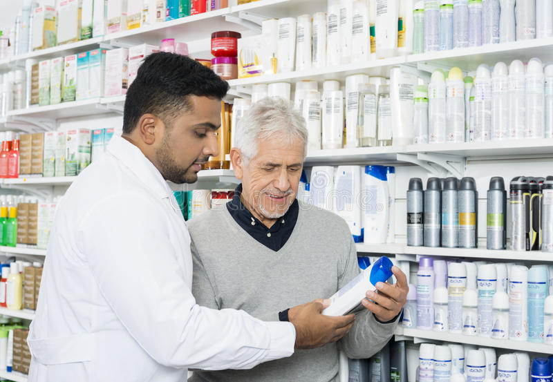 Pharmacist Assisting Customer In Buying Product stock photos