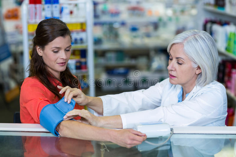 Pharmacist checking blood pressure of customer. In pharmacy royalty free stock photography