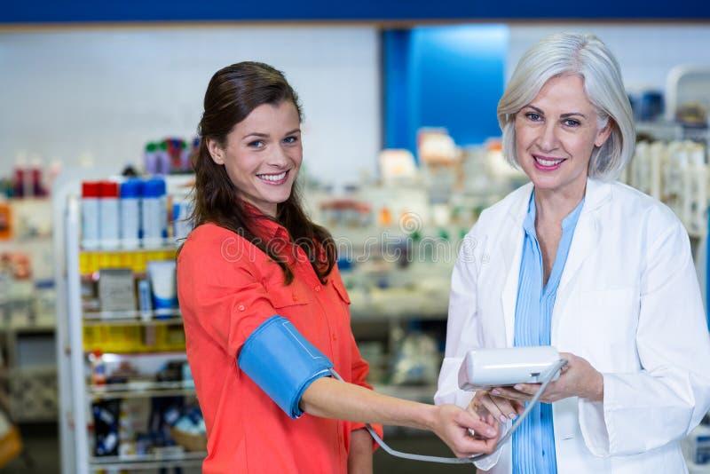 Pharmacist checking blood pressure of customer in pharmacy. Portrait of pharmacist checking blood pressure of customer in pharmacy stock image
