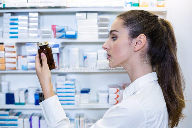 Pharmacist checking a bottle of drug. In pharmacy stock images