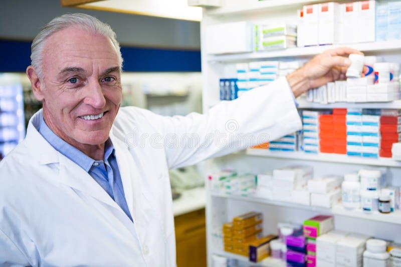 Pharmacist checking a bottle of drug. Portrait of pharmacist checking a bottle of drug in pharmacy stock photos