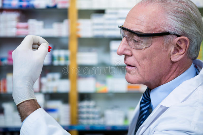 Pharmacist checking a capsule stock photography