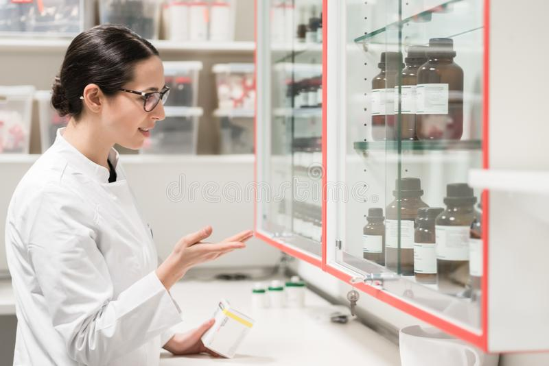 Pharmacist checking a chemical pharmaceutical substance in a modern drugstore. E view of an experienced female pharmacist checking the container of a chemical royalty free stock image
