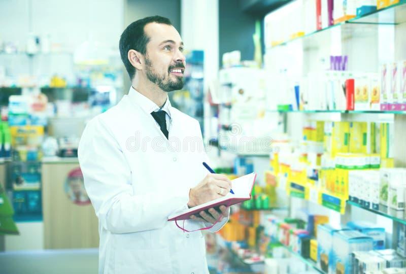 Pharmacist checking drugs in pharmacy stock photo
