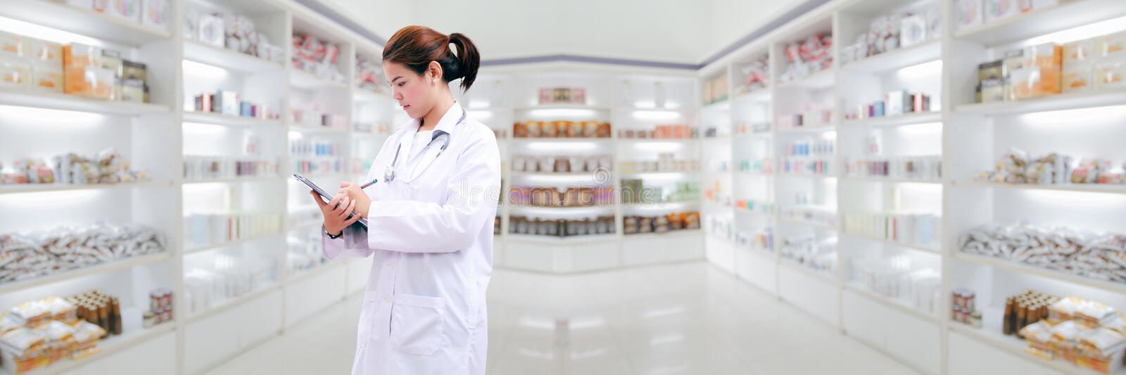 Pharmacist chemist and medical doctor woman asia with stethoscope and clipboard checking medicine cabinet and pharmacy drugstore . stock images