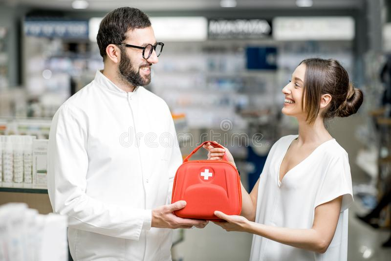 Pharmacist with client and first aid kit in the pharmacy stock images