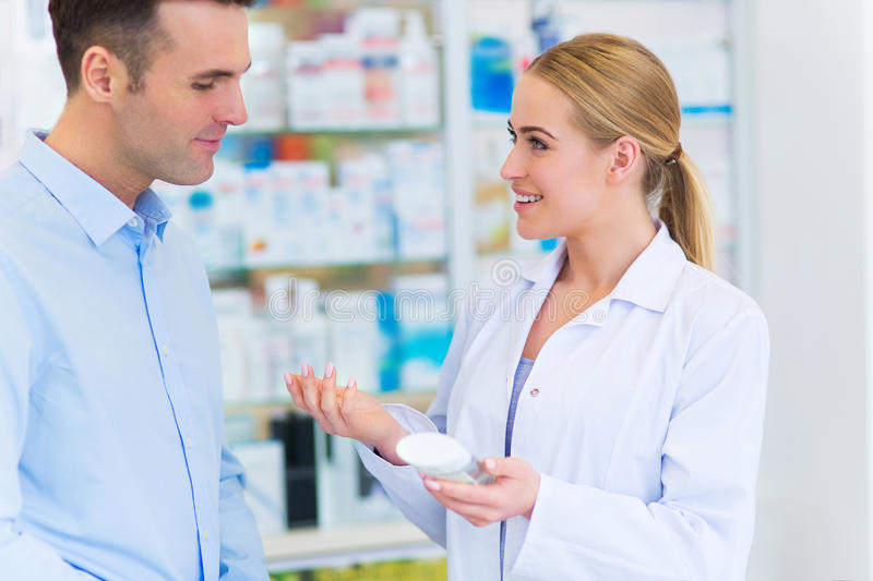 Pharmacist and client at pharmacy stock image