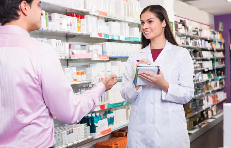 Pharmacist counseling customer about drugs. Positive women pharmacist counseling customer about drugs usage in modern farmacy royalty free stock photo