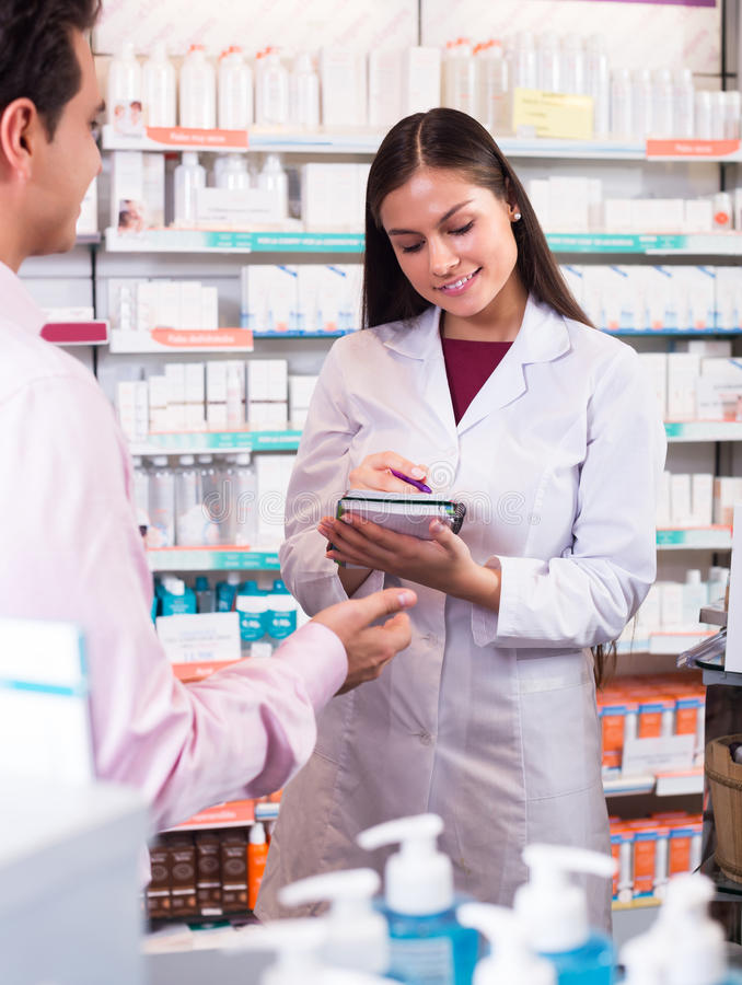 Pharmacist counseling customer about drugs. Smiling female pharmacist counseling customer about drugs usage in modern farmacy royalty free stock photography