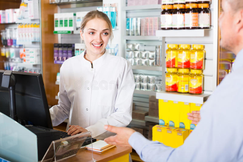 Pharmacist counseling customer. Female pharmacist counseling latin customer about drugs usage in modern farmacy stock photos