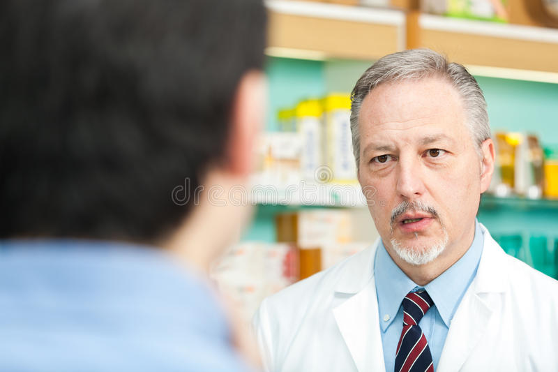 Pharmacist and customer. A customer asking for a medicine to a pharmacist stock image