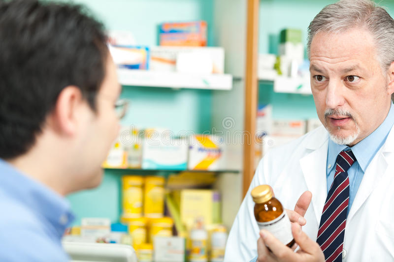 Pharmacist and customer. A customer asking for a medicine to a pharmacist stock photography