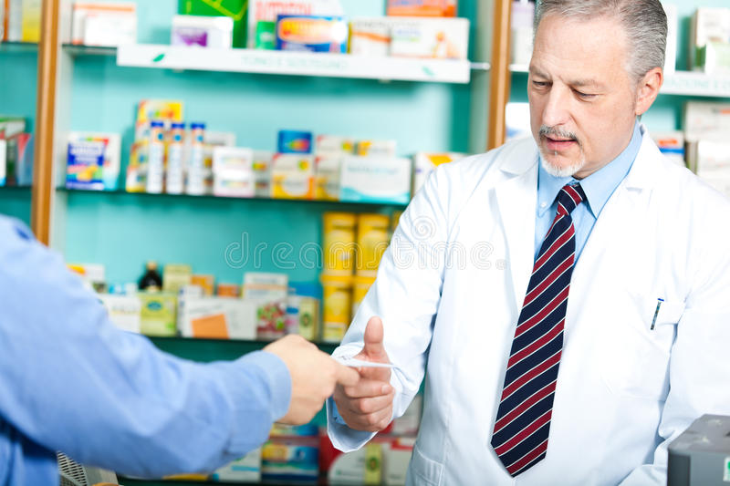 Pharmacist and customer. A customer asking for a medicine to a pharmacist stock photo