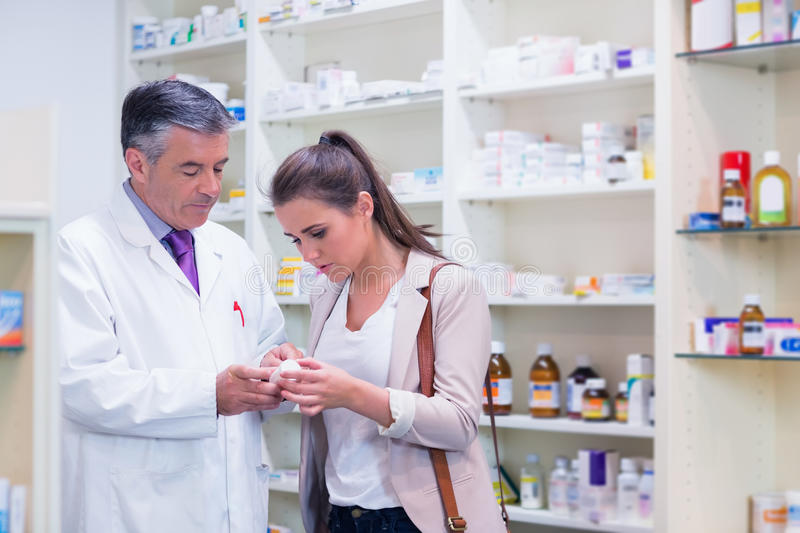 Pharmacist and customer talking about medication stock photos